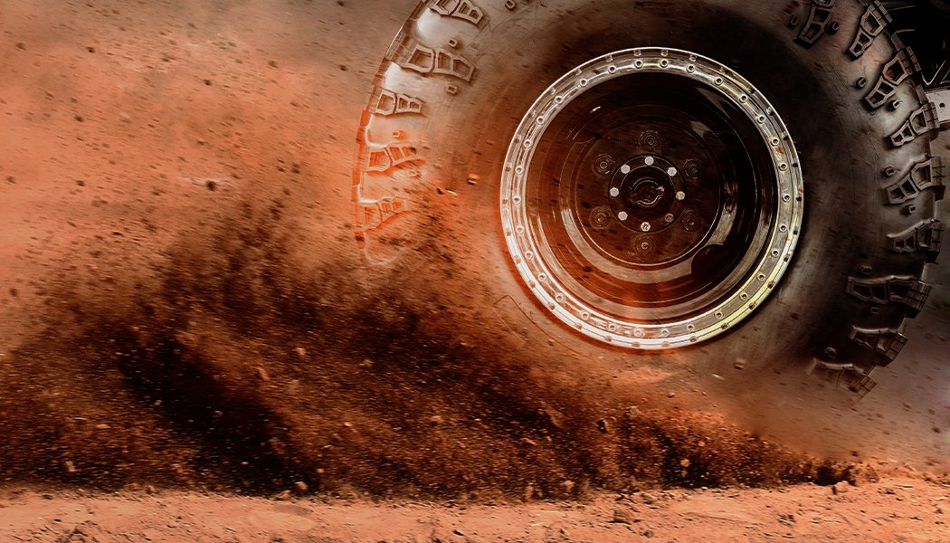 Image of a spinning wheel and flying soil.